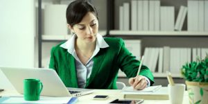 Lady sitting at desk writing on notepad